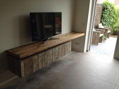 Een zwevend tv meubel. Het bovenblad is gemaakt van oude wagondelen. Gecombineerd met twee grote vrij hangende lades van sloophout.
