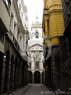 A view of an empty alley at the historical downtown of Rio de Janeiro, Brazil. It shows colonial architecture and a catholic church at the end.