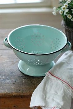 """The Enamelware Colander in Robin's Egg Blue hearkens back to simpler times, washing fruits and veggies, spending the day in your grandmother's farm kitchen. This vintage style colander gets its charm from the soft robin's egg blue shade and black trim. Food safe. 9.25"""" diam. Coordinates with our Enamelware Basin and Petite Serving Set."""