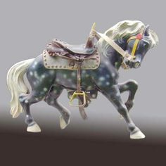 PTC - $1700  A rare petite striding horse with tucked head from the Philadelphia Toboggan Company. Now and then found pulling a pony cart or saddled for the pleasure of a tiny rider this type of horse was produced for a children's carousel. This dapple grey metal horse in good condition bears a leather western saddle with stirrups and measures 27 high x 36 long.