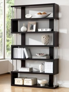 The Zhao Bookcase delivers a contemporary design inspired by classic feng shui forms. Made of wenge faux wood veneer covering engineered wood frame with chromed steel side supports. Add your favorite
