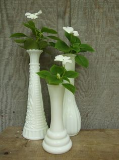 These are wonderful!    A set of three milk glass bud vases in varying sizes and styles.    The tallest:  9 tall  3 diameter base.  Nice cut