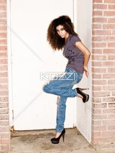 posing teen - Girl leans on the side of doorway with her leg up.   MUA - Wright Artistry