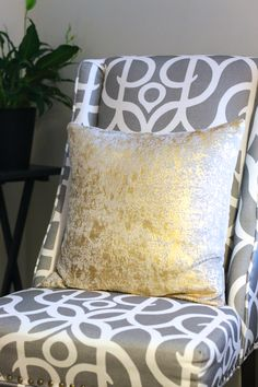 Gray and white patterned nail head trim chair with a gold metallic pillow is the perfect combo to jazz up any dull corner!