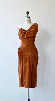 Vintage 1950s cognac velvet dress with architectural bodice, optional one or two shoulder strap, princess seaming, gathered hip and back metal zipper. --- M E A S U R E M E N T S ---  fits like: small bust: 34-34.5 waist: 26 hip: 38 length: 45 brand/maker: Charella of California condition: