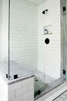 this walkin shower features natural stone tile paired with a mosaic tile inlay and flooring a builtin shower bench is convenient for leisurely bathing