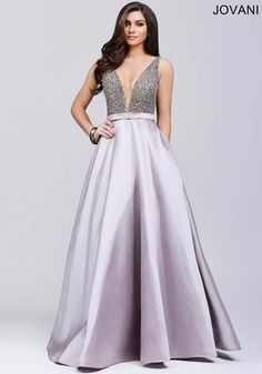 Floor length ballgown with a plunging sheer mesh neckline and beaded embellished bodice features an A-line poly satin skirt