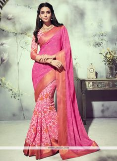 Appear ethnic with this affluent hot pink georgette printed saree. This dress is showing some really mesmerizing and imaginative patterns embroidered with patch border and print work. Comes with match...