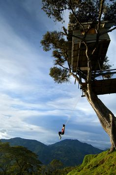 A tourist is enjoying the 'Swing At The End Of The World', an adventure destination in Banos, Ecuador.  The swing carries the swinger out over a deep mountainous canyon and is attached to a treehouse called La Casa del Arbol.  The treehouse was constructed many years ago to monitor the Tungurahua Volcano.