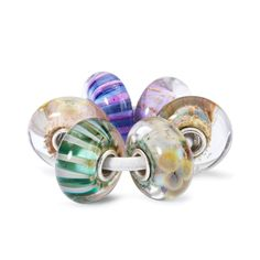 A story of volatile kisses, old legends and new possibilities. This kit contains the Rainbow Bridge Bead, the Graceful Sky Bead, the Violet Stripe Bead, the Wise Bamboo Bead, the Wild Flowers Bead and the Floral Wishes Bead.  The beads in the kit are made of Italian glass.