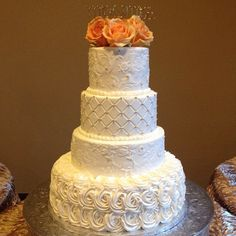 This 4 tier cake has a damask pattern on the top and 3rd tier. The 2nd tier is a grid pattern with silver dragees in the points. The bottom tier is piped roses. The top 2 tier have a piped border and the topper was made from fresh orange roses! This cake serves 155
