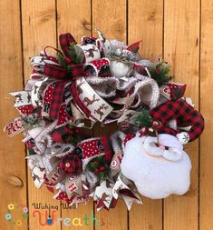 """This Buffalo Plaid Santa Wreath is covered in a snowy burlap with a fun Buffalo plaid Santa head hanging off the corner. Opposite Santa is a giant bow covered in ribbons, the ribbons include a snowy red and black print with the words """"Merry Christmas"""", a Cream ribbon covered in brown glittered deer, a red and black buffalo plaid, and a fun santa ribbon saying """"Ho Ho Ho"""". This Country styled Santa wreath is covered in white snowy ornaments with berries."""