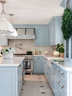 A Daltile glass tile floor and Dekton by Cosentino countertops—a surface more durable than the marble that was used on the backsplash—blend nicely with serene blue cabinetry. - Photo: Nancy Nolan / Design: Tobi Fairley