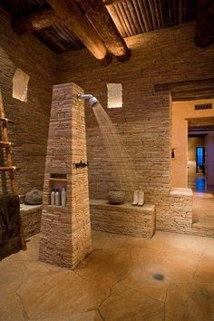 This unique bathroom is all stacked stone, stone floors and wood. The shower consists of an obelisk with a shower head above a drain.