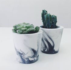 Handmade and unique pots in white porcelain cement with marble pattern in either grey or black cement.