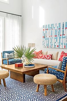 Kick traditional Americana up a notch with a palette of red, white, blue—and camel. Even the room's patterns riff on familiar American prints like the chairs' gingham-inspired cushions and the quiltlike sofa pillows. Mod, sharp-lined furnishings bring a sophisticated counterpoint to the cheery color scheme. Chair fabric: Mark Alexander's Tashkent Indigo and the rectangular sofa pillow fabric: Cowtan