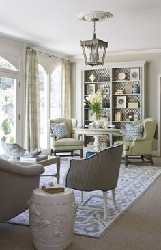 DC Design House - Elegant living room with soft gray walls paint color, yellow wingback chairs, white pedestal table, light gray painted custom built-ins with Stroheim Cranston Lattice Fabric in Granite lining the back of bookcase.