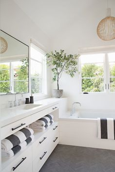 In this white and contemporary bathroom, a custom white vanity with open storage and built-in drawers, runs the length of the wall and drops down to create a built-in bathtub, while grey floor tiles in a herringbone pattern and multiple windows break up the all white room. #WhiteBathroom #ContemporaryBathroom #BuiltInBath #BathroomDesign