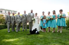 The wedding party posing with the wedding dog - bride is wearing champagne a-line dress, groom and groomsmen are wearing tan suits, and the ...