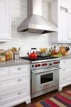 Photo: Stacey Brandford | thisoldhouse.com | from Kitchen Is a Food Hub Made for Face Time....like the hood, white brick and cabinets!
