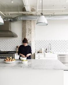 Industrial kitchen with exposed venting to outside, white subway tile backsplash and marble countertops