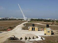 Israeli soldiers watch as an Iron Dome launcher fires an interceptor rocket.