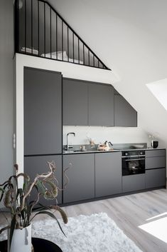 A Bright And Stylish Scandinavian Attic Apartment — THE NORDROOM - - Skylights, Scandinavian design and a loft space in a Swedish attic apartment. Bright Apartment, Duplex Apartment, Apartment Kitchen, Attic Rooms, Attic Spaces, Black Round Dining Table, Kitchen Decor, Kitchen Design, Bright Homes