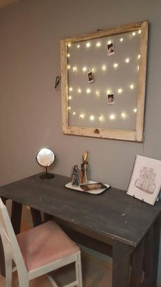 Cute string lights with clips for pictures hung inside an old window frame.