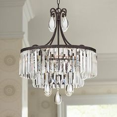 Clear crystal prisms and drops shine in the light of this timeless bronze finish 4-light chandelier.