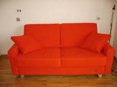 Sofá naranja muy confortable con dos cojines de lo mismo color.