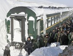 Wrong type of snow: Police prepare to shovel away snow that left a train stranded in Shangdu, Inner Mongolia