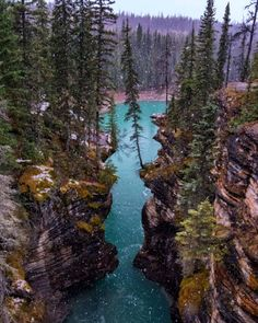 .A light snowfall over the beautiful glacial blues of the Athabasca River, Jasper National Park, la...