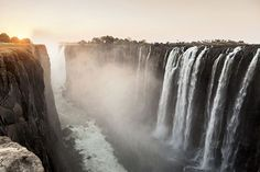 """VICTORIA FALLS, ZIMBABWE/ZAMBIA In 1855, when David Livingstone, the British explorer in Africa, came across the gigantic waterfall where the Zambezi River plunges down a 110-metre drop across a width of 1,708 metres, he named it after the reigning monarch, Queen Victoria. From time immemorial, the people indigenous to the region have known it as Mosi oa Tunya, meaning """"the smoke that thunders""""."""