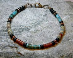 In beautiful earth tones, this southwest native style Turquoise bracelet is beaded with a picture jasper rectangle stone, turquoise nuggets, serpentine rondelles and the band is beaded with three strands of pipestone heishi. The clasp is a silver plated southwest sun burst toggle clasp.    Length: 7 1/2 (Be sure and measure your wrist to be sure this bracelet will fit)      Look for more designs in my shop here:  stoneweardesigns.etsy.com
