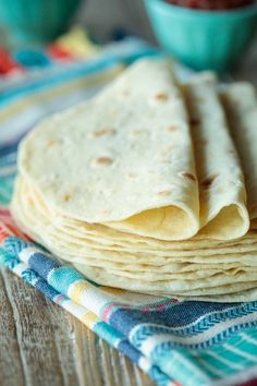 Photo of a stack or Best Ever Homemade Flour Tortillas resting on a Mexican designed cloth on a wood table.