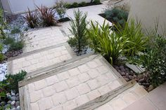 Escalier en pavés et en bois avec aménagement paysager.
