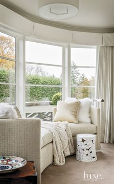 Contemporary White Bedroom Sitting Area with Curved Sofa