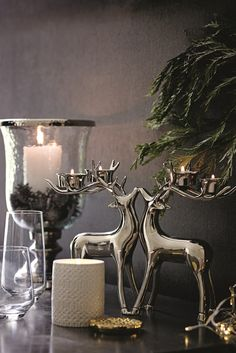 Fill your home with stylish and sophisticated seasonal ornaments and candles, including these solid silver stag candle holders.
