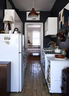 Gallery kitchen with black walls, light,  light cabinets and high cabinets