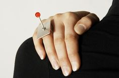 """""""Flick it"""" - ring by Sam Hamilton. Silver ring with red perspex switch, inspired by industrial machinery. The switch is movable but is kept in place by two silver rivets and tubing"""