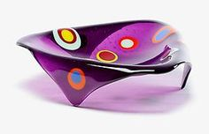 This violet triangle glass bowl is fused and then slumped so that three legs fold down from the rim. The tapered legs allow the bowl to float off the table. Multi-colored stacked circles skip around the interior of the bowl like stepping stones across a pond.