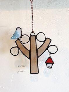木にコトリがちょこんとのったステンドグラスのオーナメントです。 小さなゆらゆらゆれるお家付きです。白い壁や窓辺などにちょこんと飾ってお使いいただくとよりガラスの色や光を楽しんでいただけます。素材 ガラス・半田・銅線・チェーン(銅古美) ガラス  薄い茶×白×水色×赤×クリア葉っぱの部分には、昭和レトロのガラスを使用しています。大きさ  木  縦横約9.3cm×8.7cm(最大幅部分) 鳥  縦横約2cm×2cm( 〃)      お家 縦横約 2.2cm×1.6cm(〃)  チェーン 約5cm●作品についてsoeur glassではガラスを使用して製作しておりますので繊細なつくりとなっております。お取り扱いの際はご注意下さい。ひとつひとつ手づくりのため若干ゆがみなどがございます。ご理解の上ご検討いただけますと幸いです。