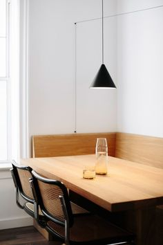 Both the corner banquette and table were custom-built in white oak and paired with a set of Cesca chairs, originally designed in the 1920s by [Marcel Breuer] (http://www.dwr.com/dining-chairs-and-stools/cesca-side-chair---cane/2020.html?lang=en_US). A matte-black cone pendant by Michael Anastassiades for Flos hangs from a long, geometrically arranged coaxial cable. The carafe and glass are by Sugahara.