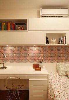 Quarto com papel de parede e escrivaninha do lado da cama