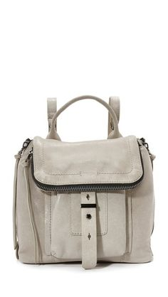 Glazed, wrinkled leather composes this mid-sized Botkier backpack. The top flap houses a zip compartment and covers the front pocket and drawstring closure. Zips open the side gussets, and the lined interior contains 2 notch pockets, 2 card slots, and a zip compartment. Top handle and adjustable shoulder straps. Dust bag included.