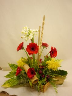 Chinese New Year arrangement  with symbolic placements and colours eg red for luck and yellow/gold for  good fortune plus the three friends of winter. Helen Allen. Verdila flowers