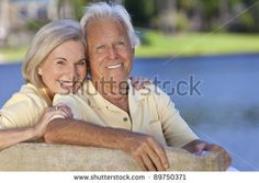 Happy smiling romantic man and woman couple sitting on a park bench embracing by a blue lake by spotmatik, via ShutterStock