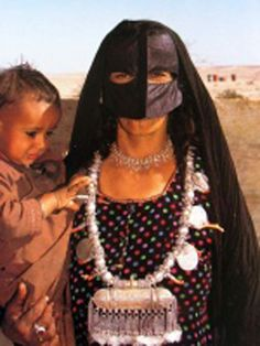 Oman | Bedouin woman with a child | Photographer unknown