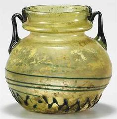A BYZANTINE GLASS JAR SYRO-PALESTINIAN, CIRCA MID 4TH-EARLY 5TH CENTURY A.D. Yellow-green in color, free blown, the bulbous body on a kicked base, the funnel mouth with an outfolded horizontal hollow rib, an applied blue-green trail wound spirally low on the body and zigzagged below, the twin blue-green handles pulled up from the shoulders, dipped onto the flange and joined to the rim 5½ in. (14 cm.) high