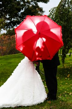 Bride and groom kissing under the red umbrella
